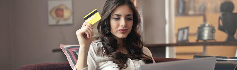 Mulher com cartão de crédito utilizando o Click to Pay